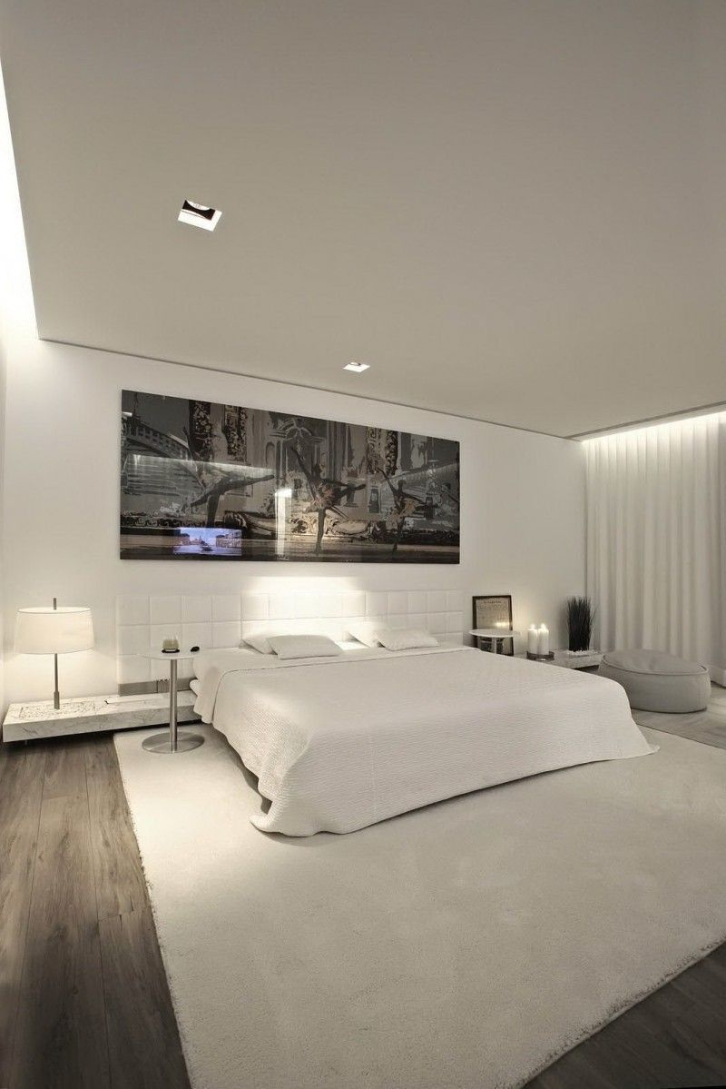 modern white bedroom with wide and low bed and soft rug