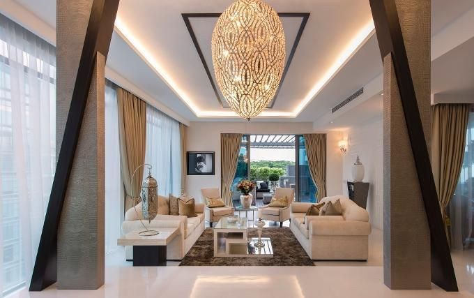 Furniture And Furnishings Play Second Fiddle To The Showstopping Light Fixture In This High Ceilinged Living Room While Placement Of Pillars Cleverly