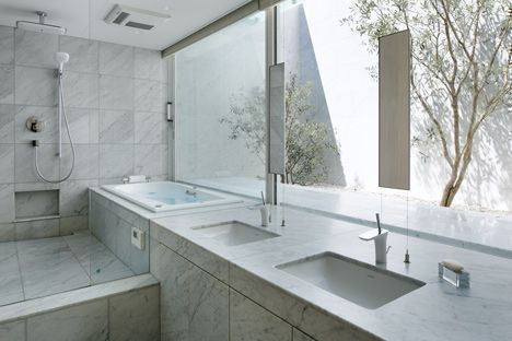 white and bright villa style modern bathroom that overlooks plants in the glass house at Hiroshima, Japan